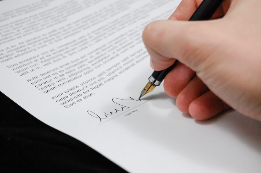 Picture of person signing a legal document.