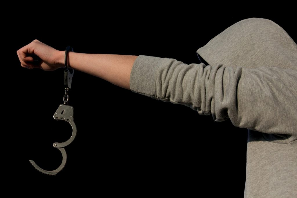 Picture of a juvenile in handcuffs demonstrating juvenile criminal defense.