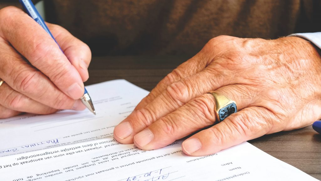 Picture of a person signing their will & testament.