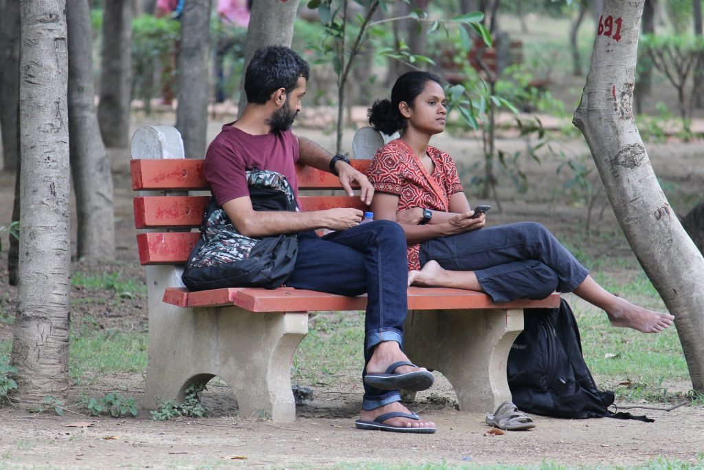Picture of a couple having an argument on a park bench.