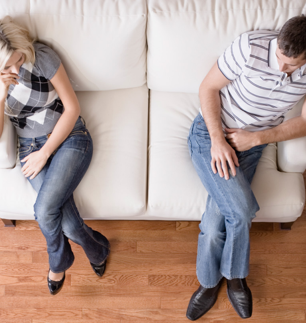 Picture of a married couple sitting on a couch and discussing divorce.