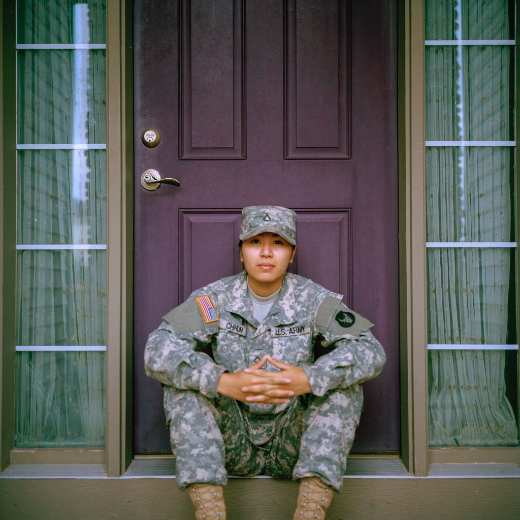 Woman in military or army uniform sits next to a closed door.